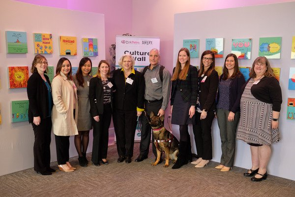 Mike, Subi, and co-workers Pose in front of the PinkPetro sponsored culture wall at the HerWorld conference.