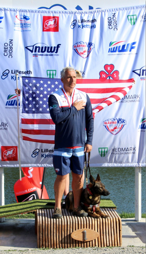 Mike and guide dog Subi on podium receiving gold metal.